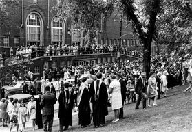people in commencement regalia stand outside a brick building