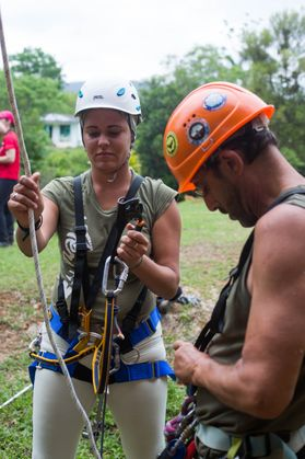 A man and woman don caving gear