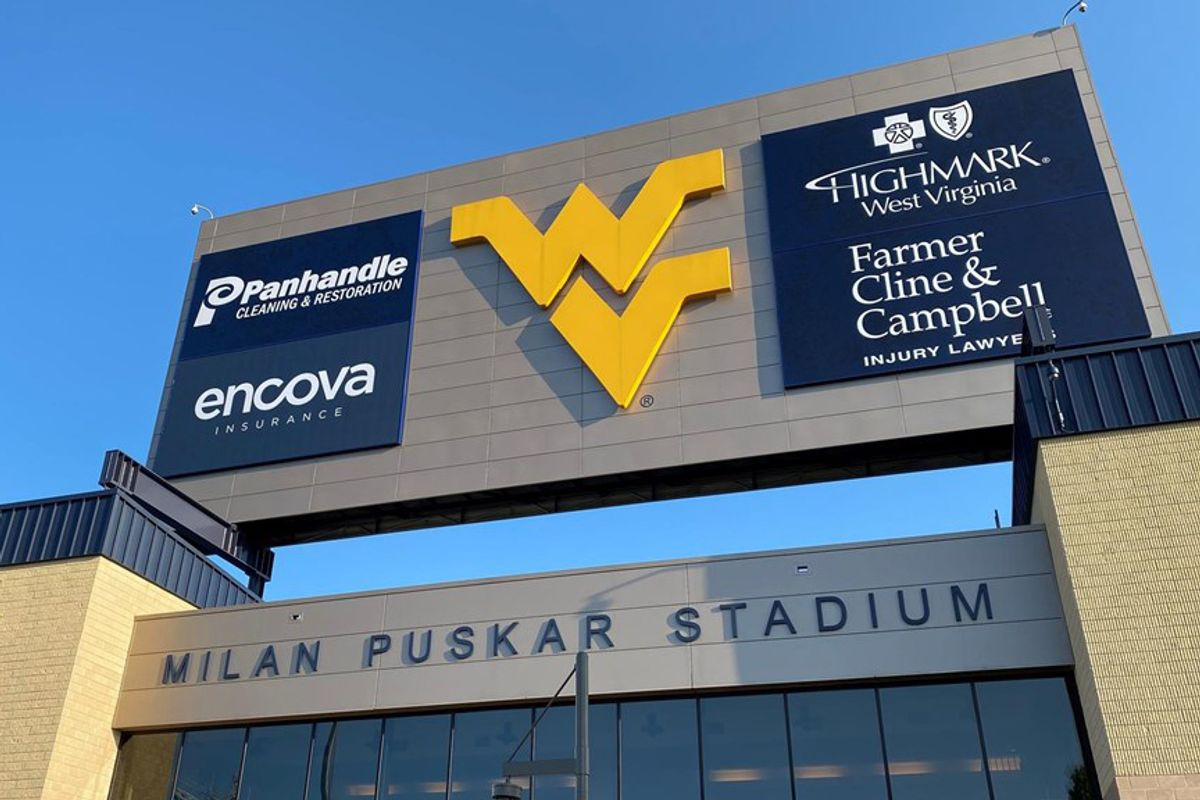 advertisements on large sign with flying WV in the center