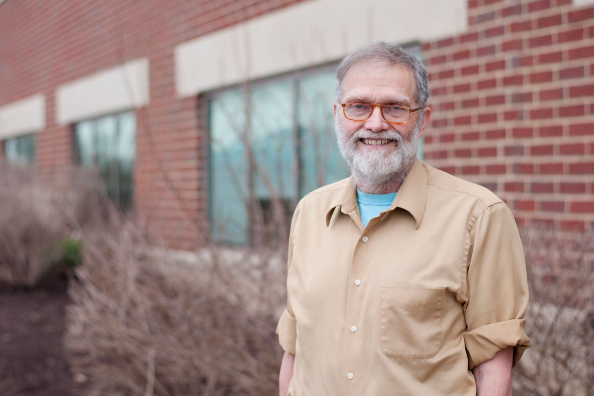 A man in a tan shirt with a light blue shirt under it, has a graying beard and glasses; he stands in front of a brick building