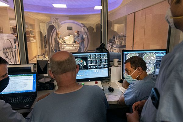 People dressed in medical scrubs behind a glass wall facing medical equipment.