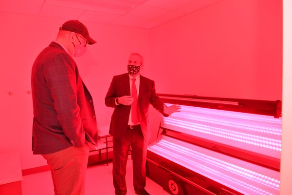 two men look at tubes of light, red cast over photo