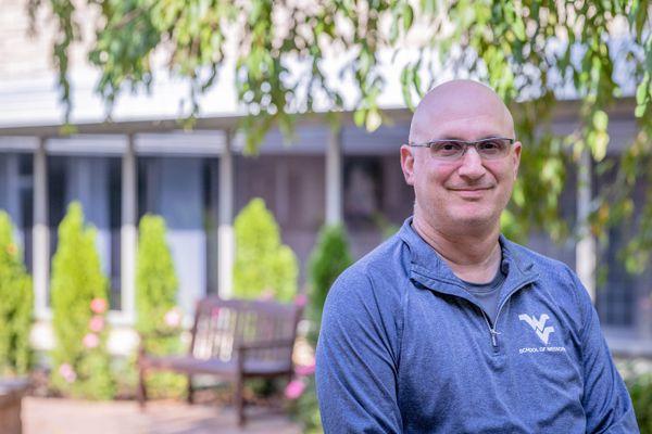 photo of bald man sitting outside