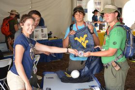 A scout receiving a patch and a WVU bag at Jambo in 2013.