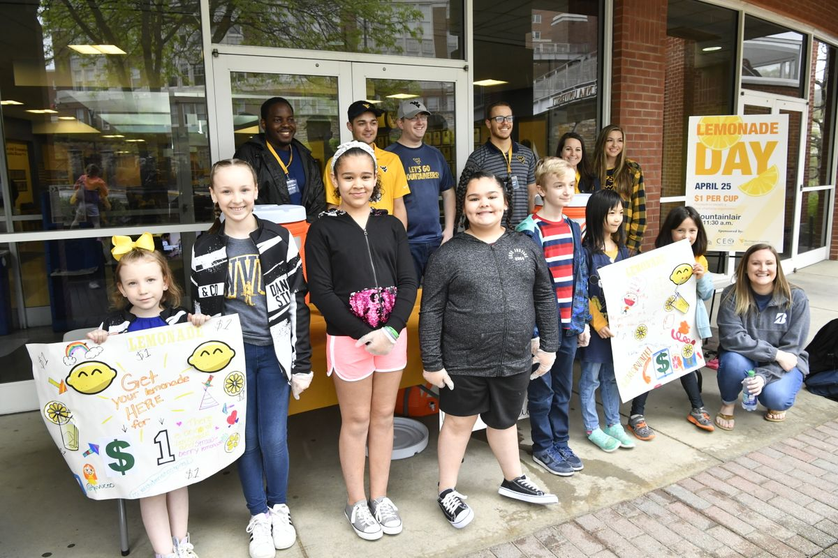 group of children stand with posters in front of young adults
