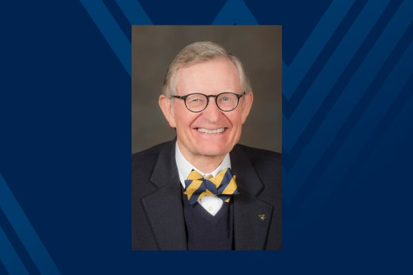 photo of man in suitcoat, vest and bowtie wearing glasses; on blue background