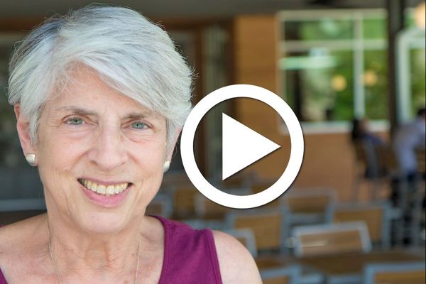 smiling woman with short gray hair, play button