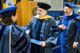 WVU 1983 School of Medicine  graduate Douglas B Learn, PhD walks and receives his diplomat 34 years later from WVU Provost Joyce McConnell, JD, LLM,  as friend Nyles Chardon PhD department of Microbiology looks on at WVU's December commencement December 15, 2017.