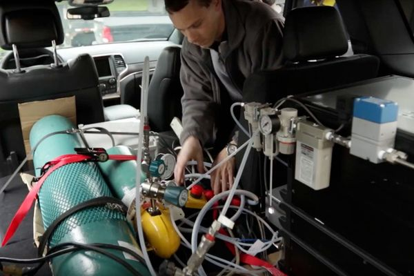 Marc Besch installs emissions testing equipment in a vehicle at the WVU CAFEE lab.
