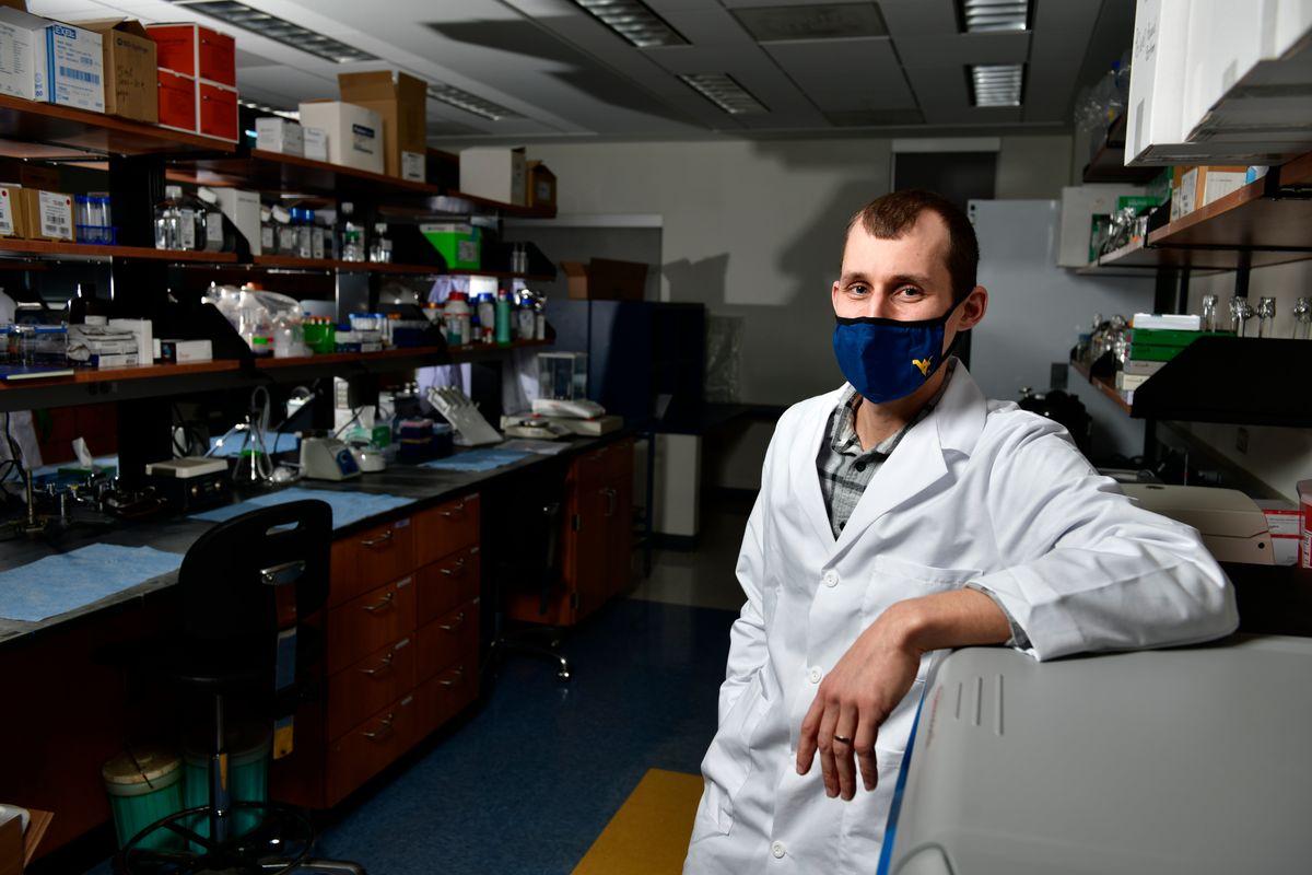 man in whitecoat stands in lab storage room