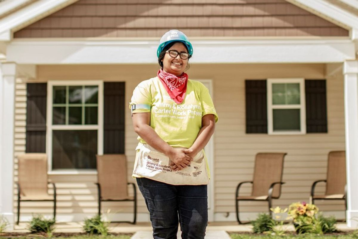 woman in hard hat stands in front of a house