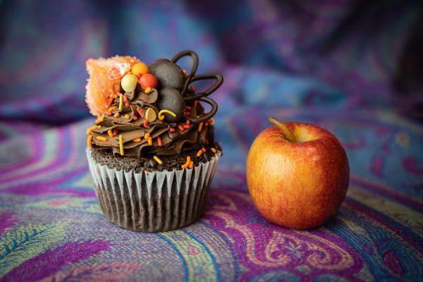 a cupcake and an apple sit on woven cloth