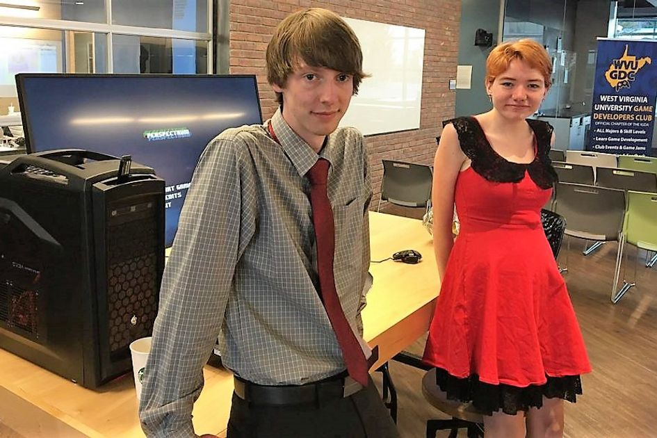Man standing in gray shirt and red tie in front of desk with girl wearing red and black dress with strawberry blonde hair