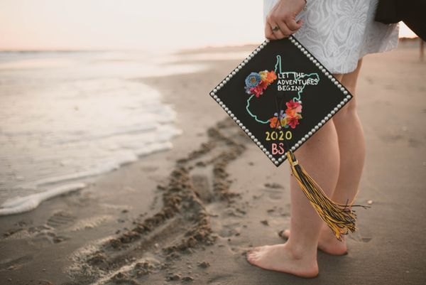 woman standing at the water's edge at the beach with a mortarboard in hand