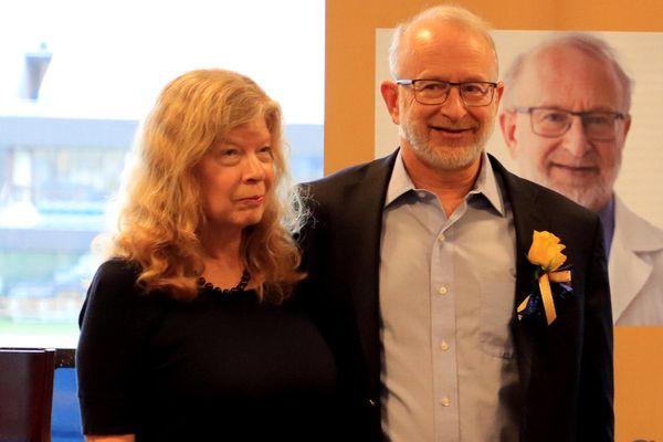 woman and smiling man wearing boutonierre