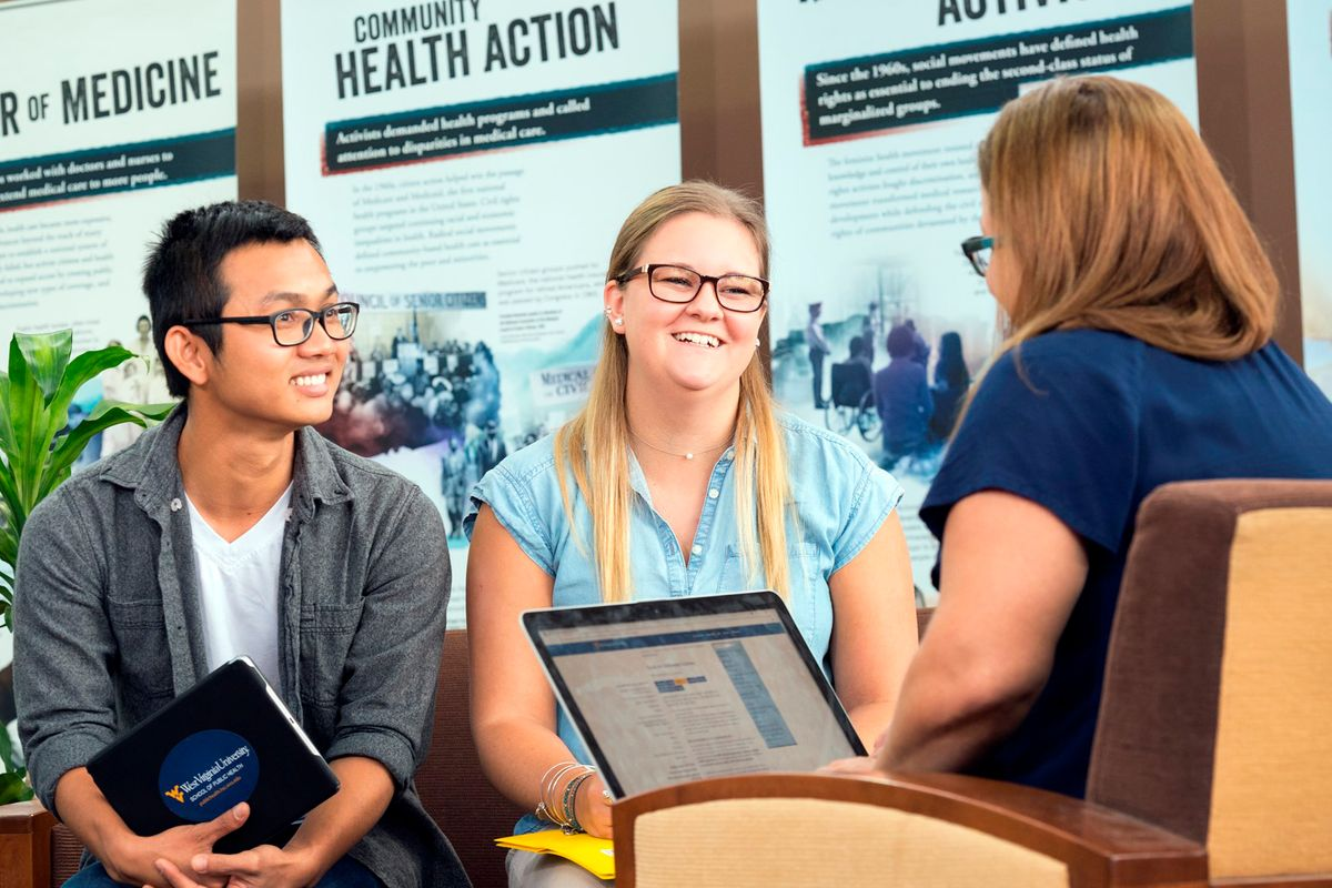 Two School of Public Health students talk with an advisor.