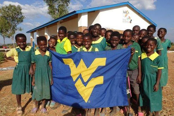 group of girls in green dress stand in front of building holding blue flag with gold letters