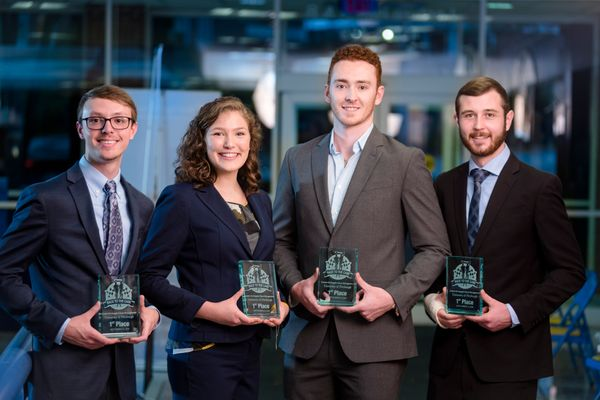 One woman and three men hold awards plaques