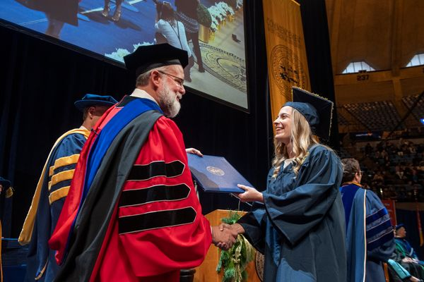 girl handed diploma by man in commencement garb