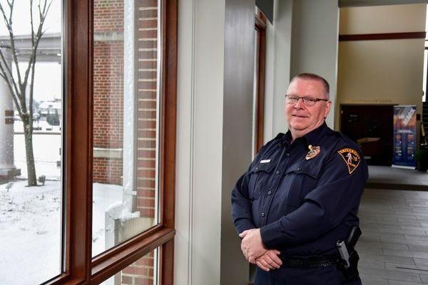 man in uniform stands near a window