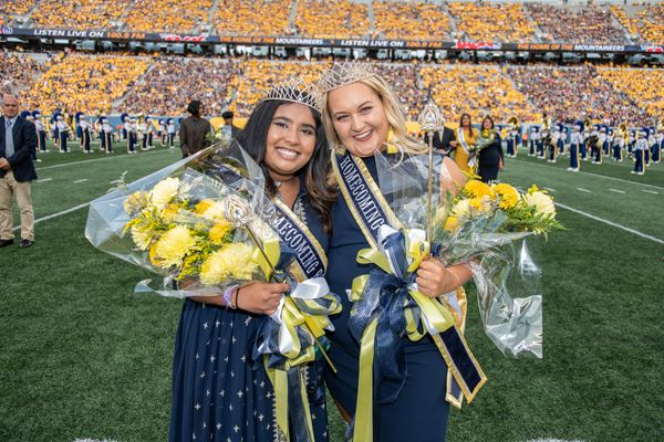 Two women stand on a football field holding flowers