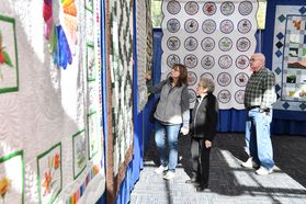 photo of people looking at hanging quilts