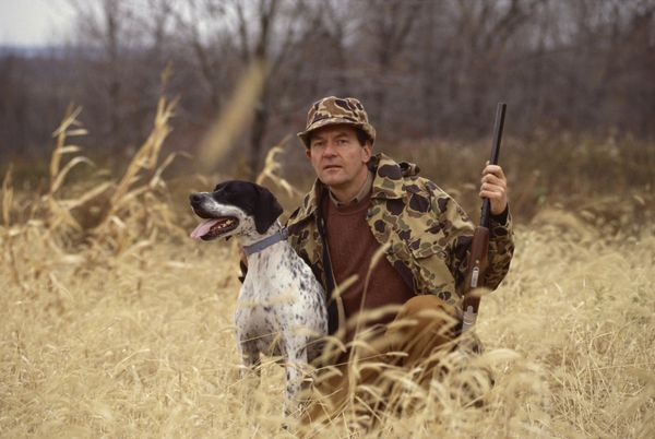 Hunter wearing camouflage kneeling next to a brown dog