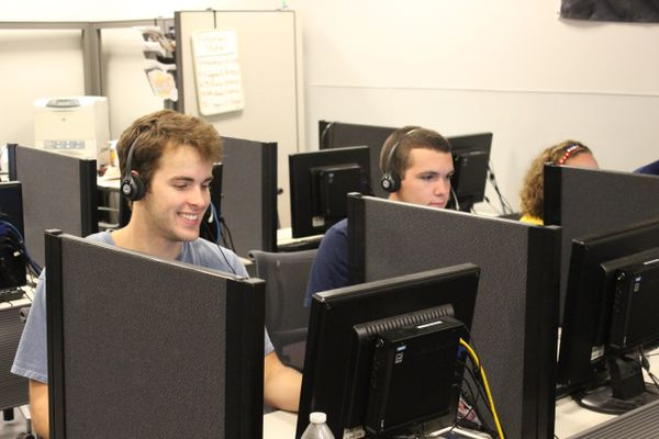 Three students sit at desks with grey partitioners and headsets on