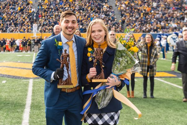 man and woman stand on a football field with flowers and small statues