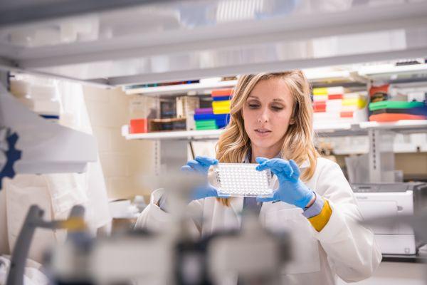 blonde woman in whitecoat, blue gloves in laboratory