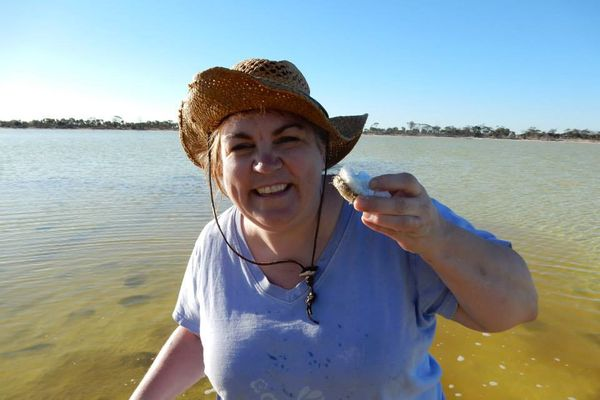 Woman in blue shirt and brown hat stands in a yellow and green body of water, holding up a white sea creature