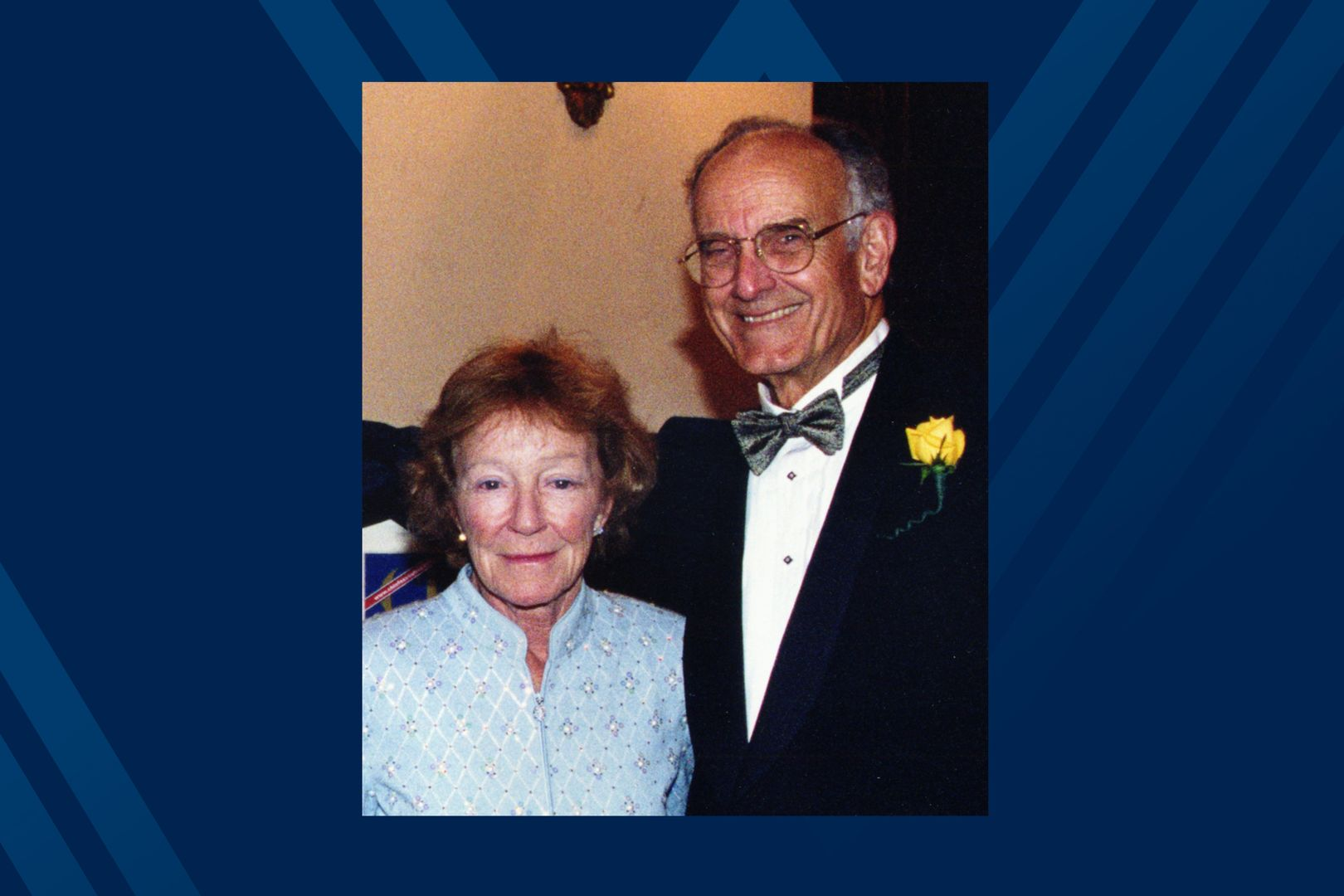 older couple in formal clothing on blue background