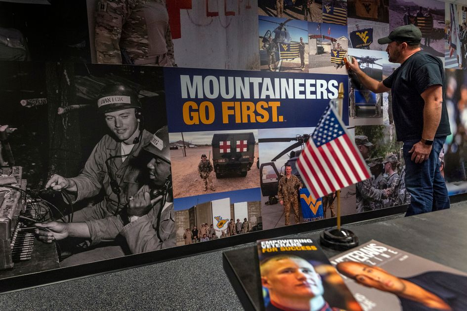 Jani Horvath wraps the wall of the WVU Veteran and Military Family Support Headquarters with military lifestyle scenes. The Support Headquarters located in the WVU Mountainlair will provide academic and social support to student veterans and their families.