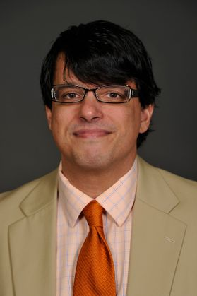 man with glasses and black hair in beige suit