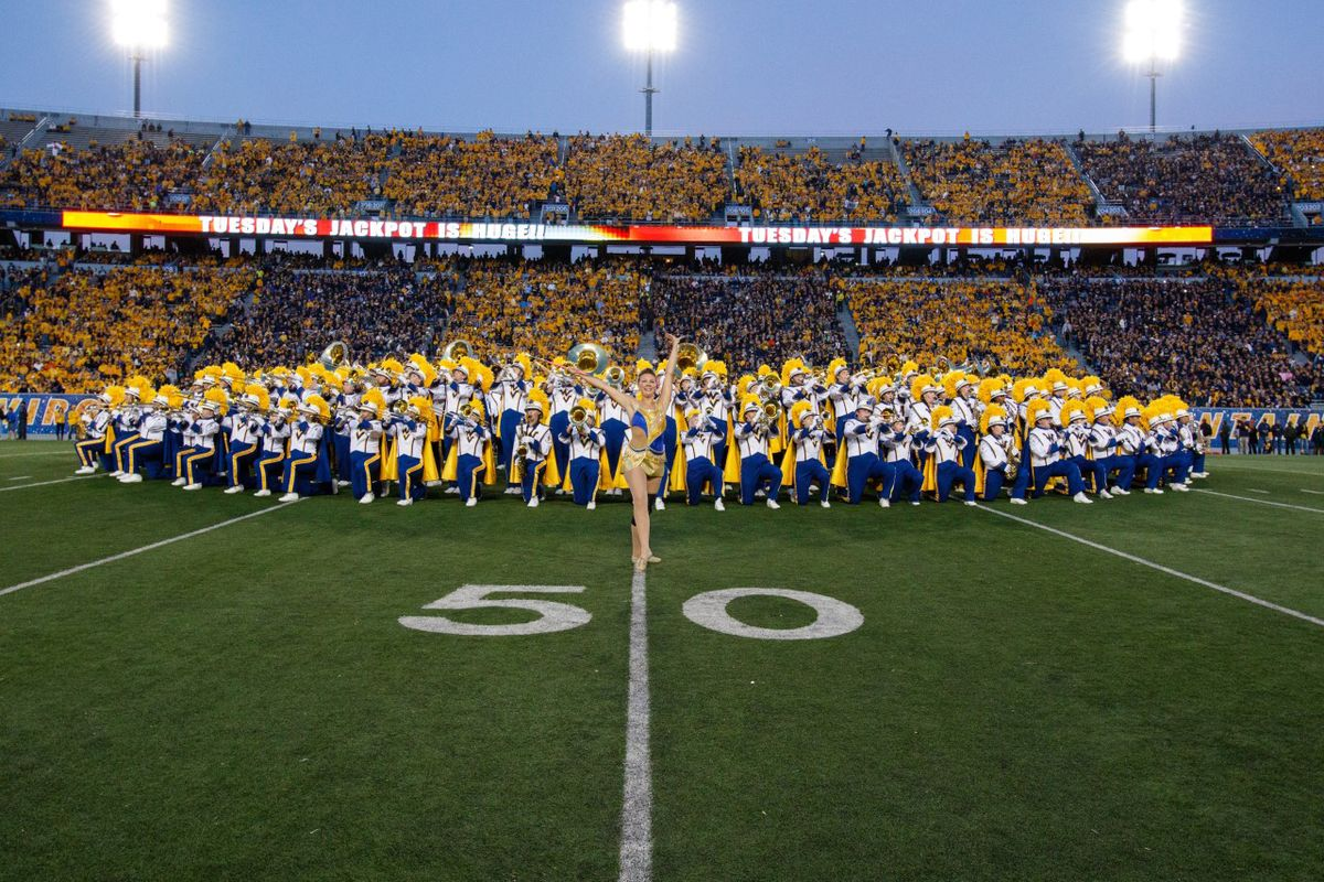 twirler stands posed in front of large marching band in full stadium striped gold and blue