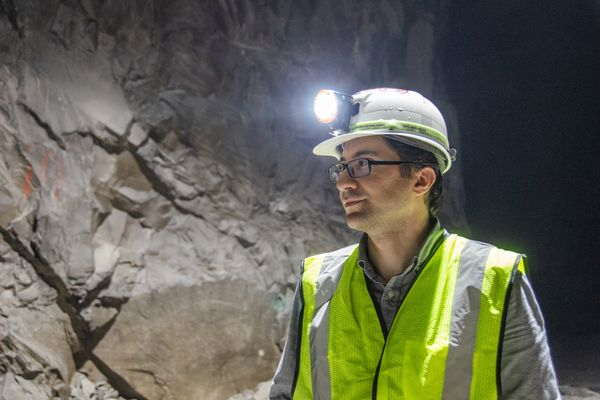 man in glasses, hardhat with light, fluorescent vest