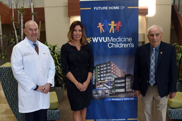 Two men and one woman flank a popup banner that says WVU Medicine Children's