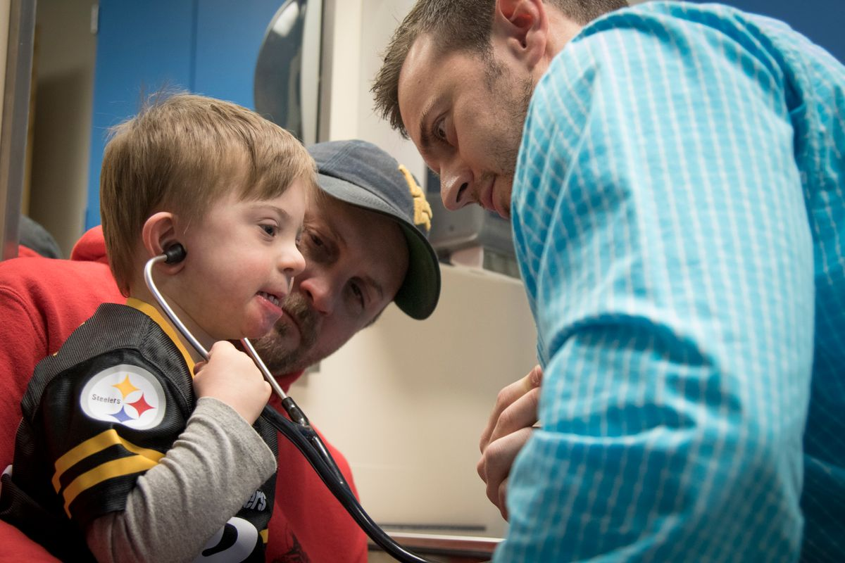A child tries out a stethoscope while sitting on an adult's lap. Another man is also in the photo.