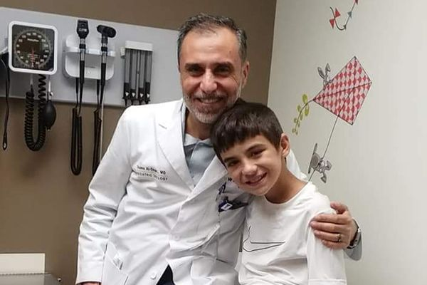 a medical professional sits with his arm around a pediatric patient