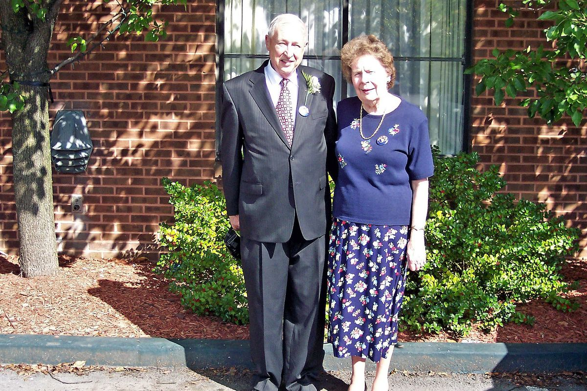 man in suit and tie, woman in sweater/skirt combo in front of brick wall, window
