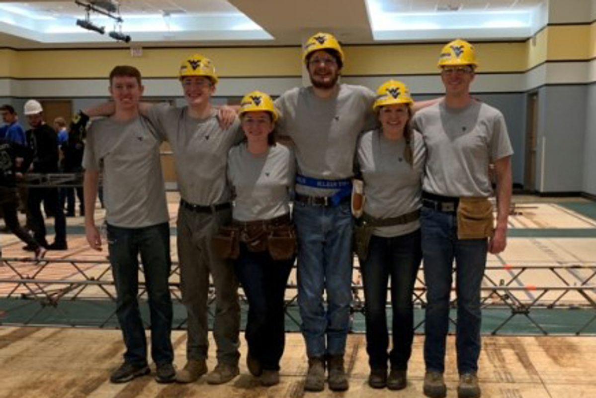 Six people wearing grey shirts and yellow hard hats
