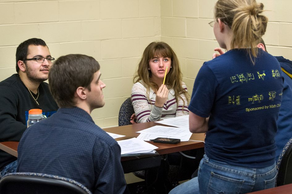 Four students sitting at desk talking around papers