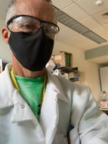 man in lab coat and mask