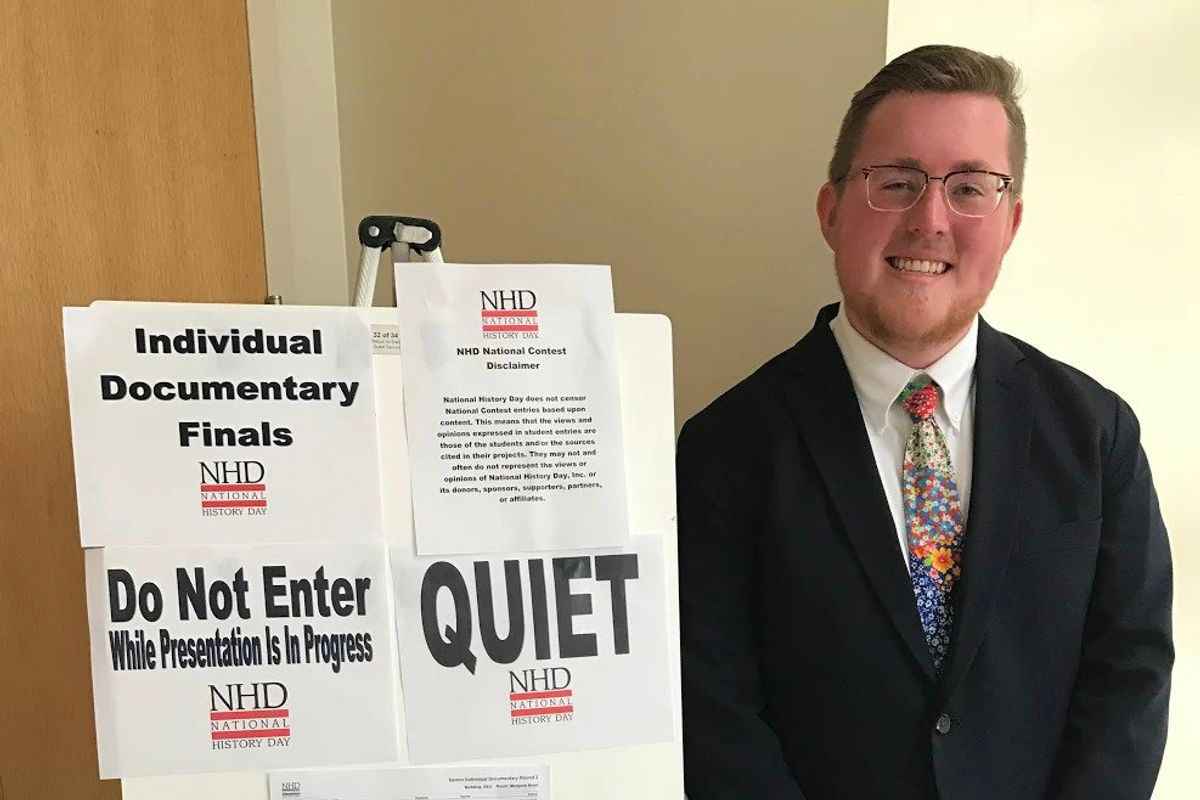 Brennan Lawless wearing black suit and glasses standing next to a bulletin board