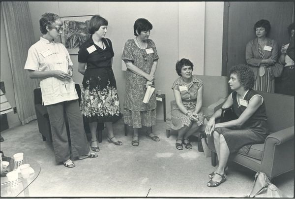 Black and white photo of women sitting in room, talking