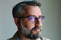 Man with dark grey hair and beard wearing glasses with a straight face