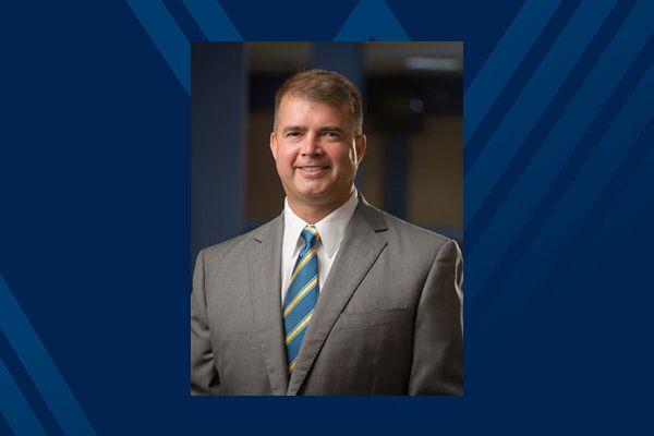 smiling man, suit, tie, blue backgroud