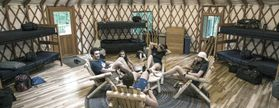 People sit in the commons area of a yurt
