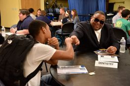 Man wearing black shirt and sunglasses fist bumps student wearing white shirt and black backpack while sitting at a desk