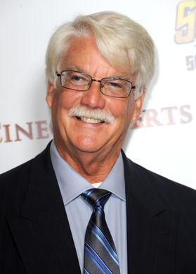 Photo of smiling man with white hair and mustache wearing dark suit jacket, blue shirt, blue and black striped tie, glasses